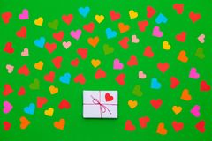 Packaged gift box on a green background with many multicolored hearts around stock image