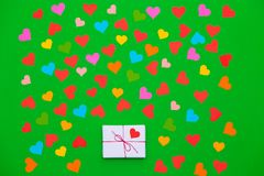 Packaged gift box on a green background with many multicolored hearts around stock photo