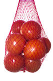 Packaged tomatoes hanging in red plastic net. Isolated over white background stock image