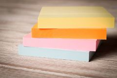 Packages of colorful stickers for notes on a wooden table.  stock photos