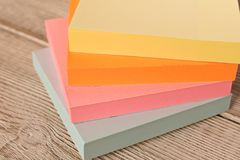 Packages of colorful stickers for notes on a wooden table stock images