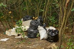 Packages and garbage bags among plants in the nature Royalty Free Stock Images