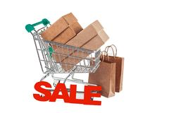 Packages with purchases and a supermarket trolley on a white bac. Packages and boxes with purchases and a supermarket trolley and an inscription SALE on a white Royalty Free Stock Photography