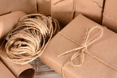 Packages and Twine. Closeup of a group of packages wrapped with plain brown paper and twine. Horizontal format on a wood table royalty free stock photos