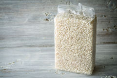 Packaging with Arborio rice on wooden boards. Horizontal Stock Photo