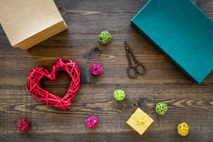 Packaging gift. Colored gift boxes, sciccors, thin cord on dark wooden background top view Stock Photos