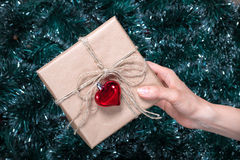 Packaging holiday gifts.Young girl gives a Christmas gift with decorations. Top view. Packaging holiday gifts.Young girl packs a Christmas gift with Christmas Royalty Free Stock Photos