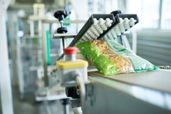 Packaging Line at Food Factory. Close up of production process at modern food factory, focus on macaroni bag ready for packaging sliding down assembly line, copy stock photography