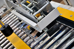 Packaging machine of manufacturing. Packaging machine in manufacturing industry, including many rolls and frame, shown as a manufacturing equipment, working Stock Photos