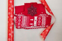 The packaging process of the red with white pattern knitted sweater. Wrapping paper with snowflakes. Horizontal. stock images