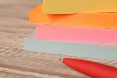 Packar av färgrika klistermärkear för anmärkningar och en penna på en trätabell arkivbild