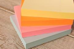 Packar av färgrika klistermärkear för anmärkningar på en trätabell arkivbilder