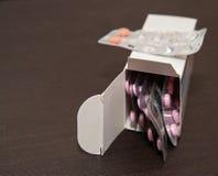 Packar av preventivpillerar på brun träbakgrund arkivfoton