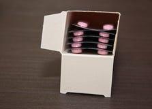 Packar av preventivpillerar som isoleras på brun träbakgrund arkivbilder