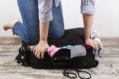 Packar för ung flicka svärtar tillfälligt resväskan Arkivfoton
