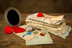 Packe av bokstäver och den tomma fotoramen Arkivfoton