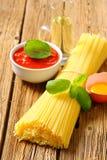 Packe av den torkade spagetti, tomatpassataen och ägget Royaltyfri Foto
