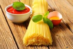Packe av den torkade spagetti, tomatpassataen och ägget Arkivbilder