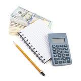 Packe av dollar, räknemaskinen och anteckningsboken Arkivbild