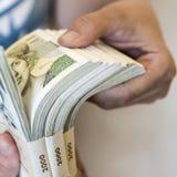 Packe av pengar - stor hög av sedlar i hand fotografering för bildbyråer