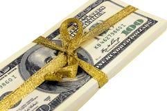 Packe av räkningar av hundra dollar som binds med ett guld- band dollar som isoleras på vitbakgrund Royaltyfri Bild