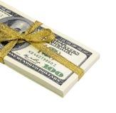 Packe av räkningar av hundra dollar som binds med ett guld- band dollar som isoleras på vitbakgrund Arkivfoto