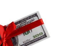Packe av räkningar av hundra dollar som binds med ett rött band dollar som isoleras på vitbakgrund Arkivbild