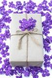 Packe för gåvaask som slås in med papper och repet med purpurfärgade blommor Royaltyfria Bilder