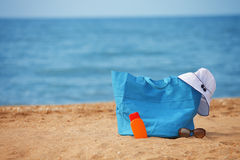 Packed beach bag on empty sand beach Royalty Free Stock Image
