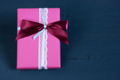 Packed box, gift on a wooden dark-blue background. Selective focus, small depth of field, toned image, film effect Royalty Free Stock Photo