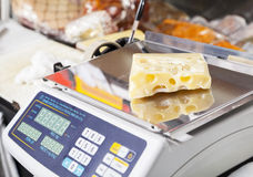 Packed Cheese On Weight Scale In Store. Packed cheese on weight scale in grocery store Royalty Free Stock Photography