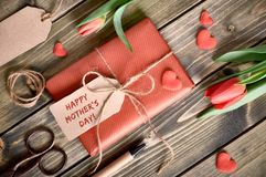 Packed gift box, cord, scissors, tags and decorative hearts on w Royalty Free Stock Images