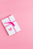 Packed gift with small heart on a pink background. Selective focus, top view, macro, toned image, film effect. Packed gift with small heart on a pink background Royalty Free Stock Images