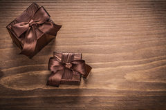 Packed glittery gift containers with bows on vintage wooden boar Royalty Free Stock Photo