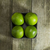 Packed limes on a wooden background. Four packed limes on a wooden background royalty free stock image