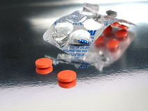 Packed orange medicines. In a silver background Royalty Free Stock Photos