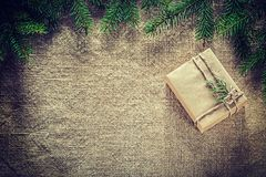 Packed present box thuya fir tree branch on sacking surface.  Royalty Free Stock Images