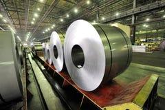 Packed rolls of steel sheet. Inside of shipyard Stock Photos