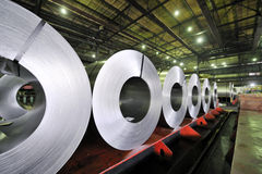 Packed rolls of steel sheet. Inside of shipyard Stock Images