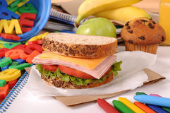 Packed school lunch: sandwich, apple, cake on classroom desk Royalty Free Stock Image