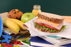 Packed school lunch: sandwich, apple, drink on classroom desk Royalty Free Stock Photos
