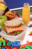 Packed school lunch: sandwich, cake, apple and drink on classroom desk Stock Photo