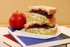 Packed school lunch: turkey sandwich, apple, on classroom desk Stock Image