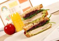 Packed school lunch: turkey sandwich, apple, drink on classroom desk Stock Images