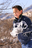 Packed snow ball. Boy with snow on jacket running with a large packed snow ball Stock Photo