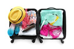 Packed suitcase with summer clothes and accessories on white background. Top view stock image
