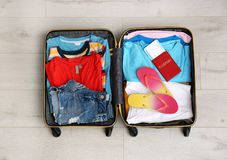 Packed suitcase with summer clothes and passport on wooden background. Top view stock photography