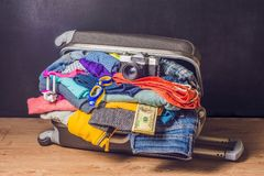 Packed suitcase with travel accessories and money on wooden back. Ground Royalty Free Stock Image