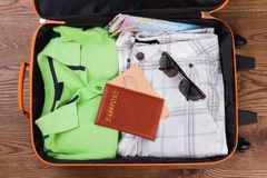 Packed suitcase for travel flat lay. Folded male clothes with sunglasses and passport Royalty Free Stock Image