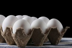 Packed white eggs on dark background close up.  royalty free stock image